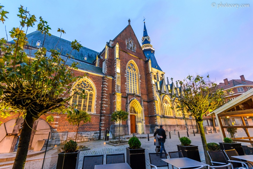 Evening blue sky with a shade of pink, the yellow lights and red bricks of the cathedral and the green leaves of the trees create a magical atmosphere