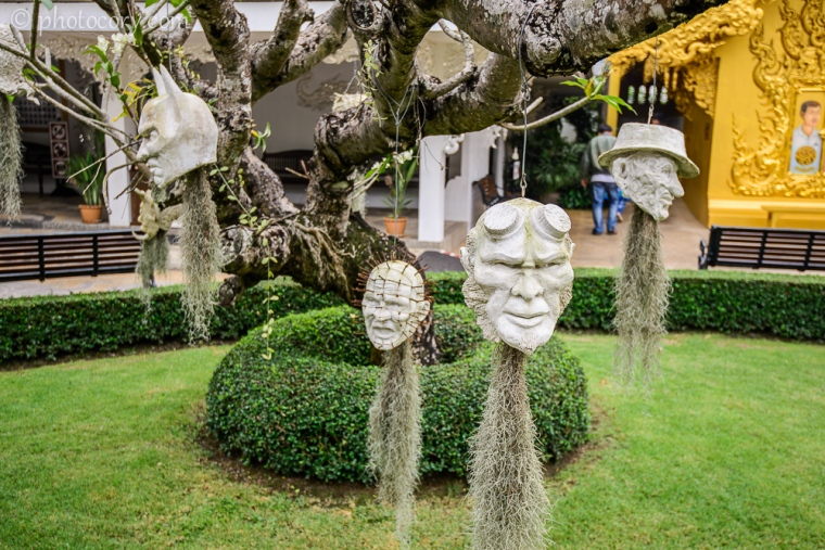 Ghost heads hanging from the trees in the garden of the White Temple