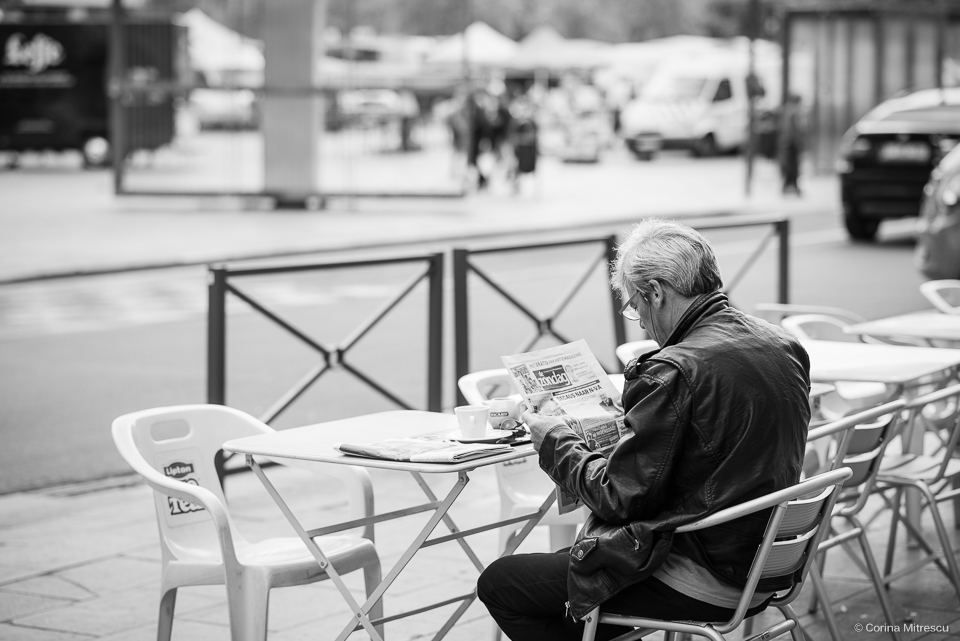 man reading newspaper on a corner coffee shop