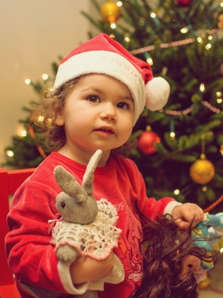 child next to christmas tree