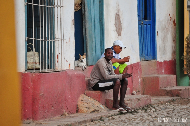 men and dog on stairs trinidad cuba