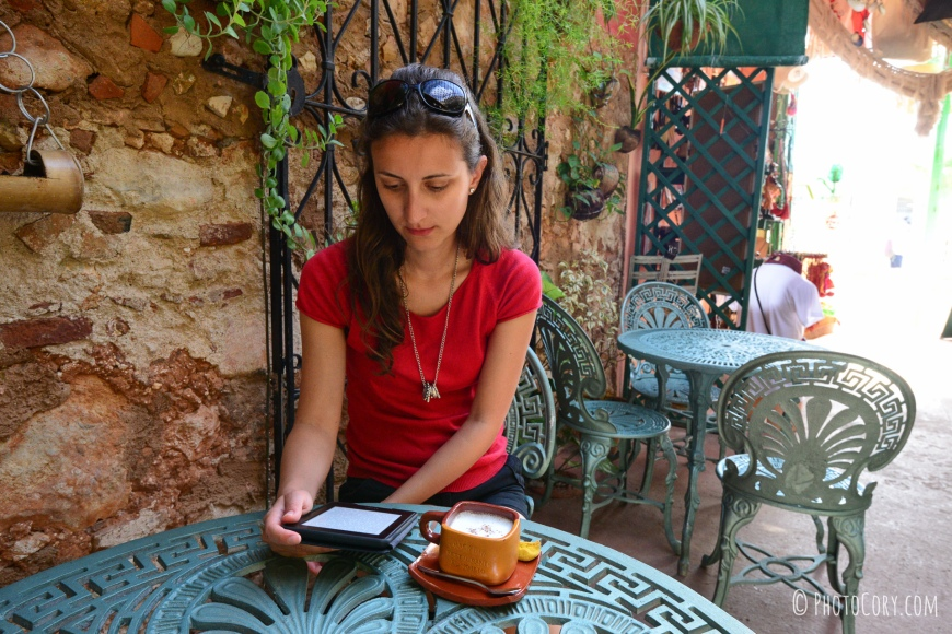 reading from kindle in cafe restaurant plaza mayor trinidad cuba